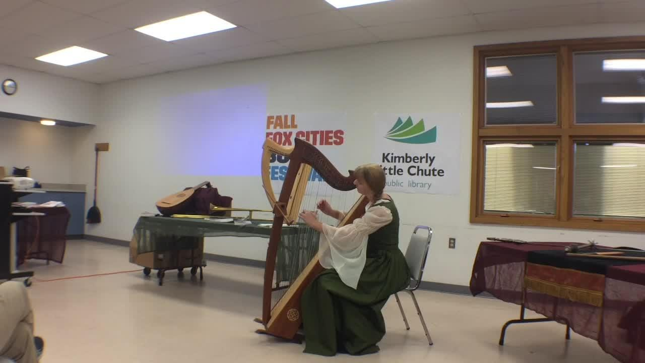 """Author Laura Vosika reads from one of her books, """"Blue Bells of Scotland,"""" and plays a Celtic tune for attendees at the Fox Cities Book Festival."""