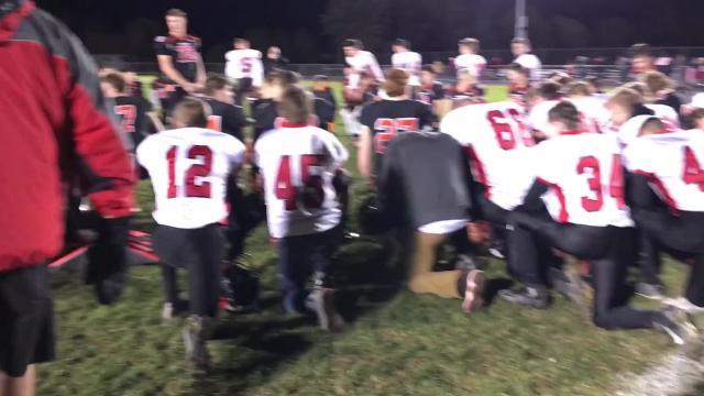 Cedar Grove-Belgium and Valders football players pray following their playoff game.
