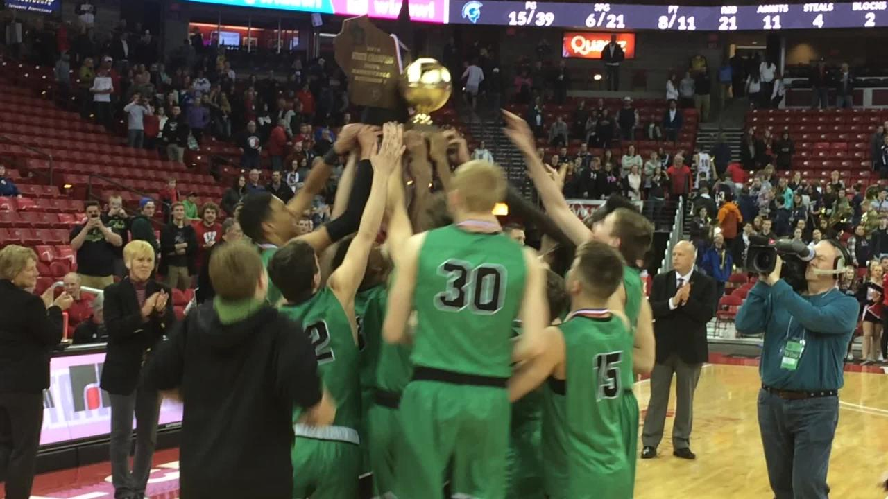 Oshkosh North coach Brad Weber accepts the Division 1 state championship trophy after the Spartans beat Brookfield East on Saturday at the Kohl Center in Madison.