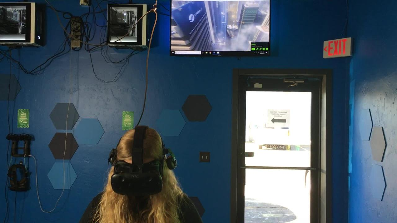 Green Bay Press-Gazette reporter Shelby Le Duc takes one step too many during her first virtual reality experience at Edge VR Arcade in Ashwaubenon. March 19, 2018.
