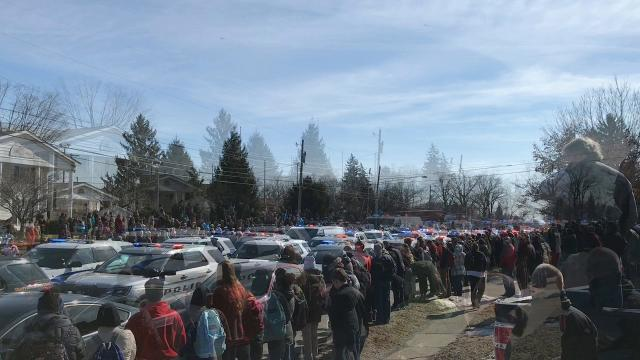 State Street in Westerville is lined with people as the procession for fallen Westerville police officers Eric Joering and Anthony Morelli comes to a stop in front of Hill Funeral Home Monday afternoon.
