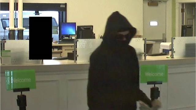 A woman wearing a black face mask black hoodie and jeans and carrying a bag entered Huntington Bank on Ashland Road and asked for money.