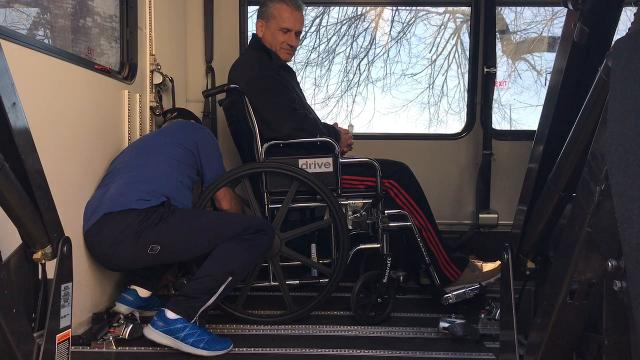 Driver Warren Courtney and Mobility Manager Nic Carey of the Coshocton County Coordinated Transportation Agency demonstrate how the shuttle's wheelchair lift works with Coshocton County Commissioners Gary Fischer as a test subject.