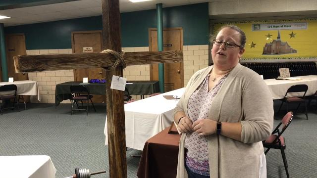 Pastor Christy Bowers of Grace United Methodist Church describes two Stations of the Cross stops. One features nailing a sin to a cross and the other drinking red wine vinegar as Christ was given vinegar to drink while on the cross.