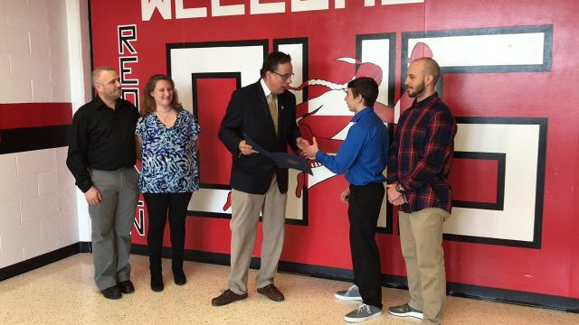 Bob Kalish of the Ohio Secretary of State's Office presents a proclamation to Coshocton High School sophomore Lucian Brink in honor of him coming in as runner-up in the Division III 106-pound state wrestling tournament.