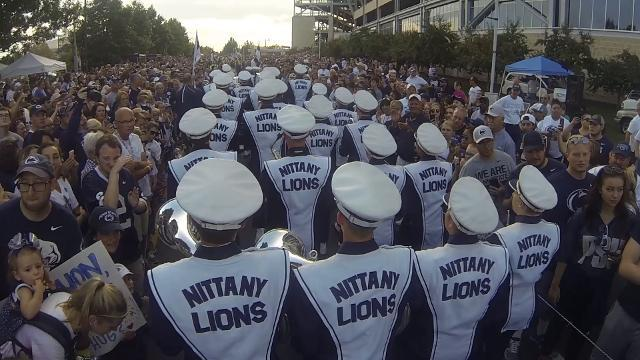 Penn State's Blue Band leads the players through long lines of screaming fans