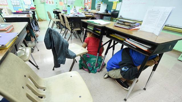 "Students ""Drop, Cover and Hold On,"" as they participate in the Great ShakeOut earthquake drill at Pedro C. Lujan Elementary in Barrigada on Thursday, Oct. 19, 2017."