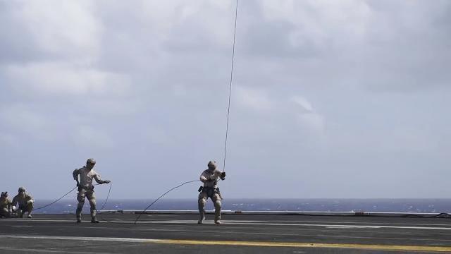Sailors rappel from a Sea Hawk