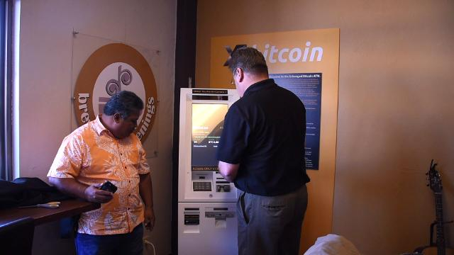 A bitcoin is purchased on Guam's first bitcoin ATM by Bitcoin Technology Consultants co-owner David McConkey at Brewed Awakenings on Dec. 9, 2017.