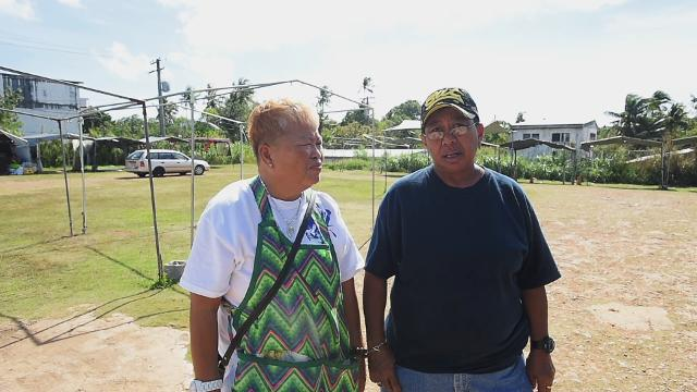 Vendors of the Old Dededo Flea Market discuss being shut down by Guam Department of Revenue and Taxation compliance officers on Jan. 20, 2018.