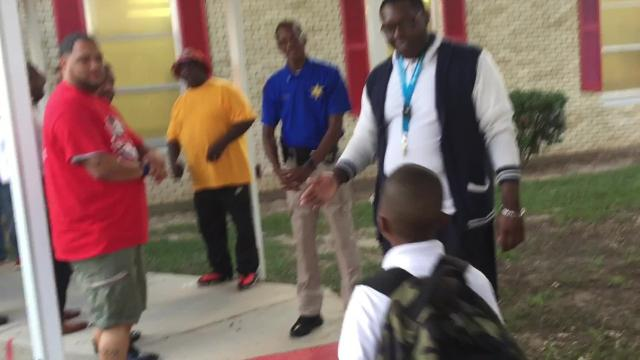 A group of men from the community form two lines to welcome students with high fives as they enter Robinson Elementary in Monroe on August 18, the first Friday of the school year.