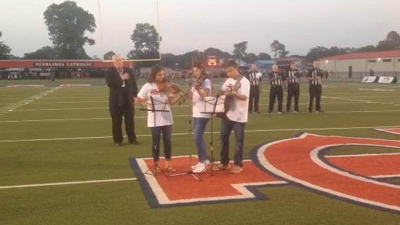 Adeline Miller, Buddy LeBlanc and Leiton LeBlanc perform the national anthem on fiddles before the start of the Teurlings High football game against Rummel.