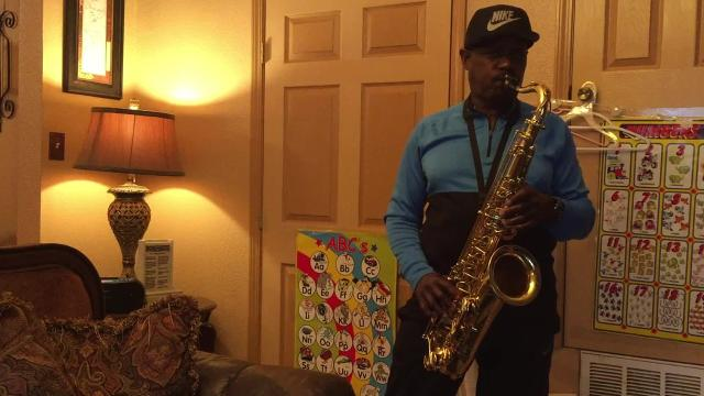 Donald Givens practices saxophone in his yard daily.