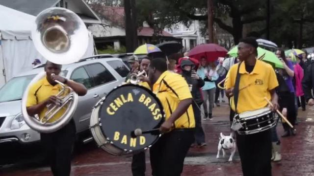 The Cenla Brass Band leads the 4th annual Garden District Promenade through streets as they collect non-perishable food for the Food Bank of Central Louisiana. The promenade was models after the Courier de Mardi Gras where people traveled through an area asking for ingredients to make a gumbo.