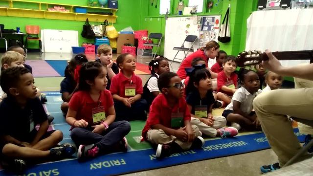 Daniel Gale, with guitar, and Jessica Eyster teach students a French song in the Acadiana Symphony Orchestra's Do-Re-ME! program, which helps children learn through music.