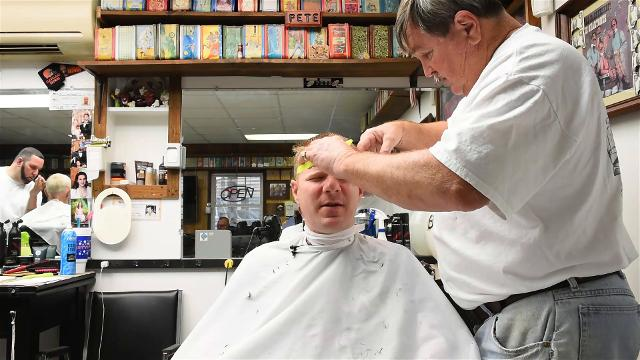 "Reporter Jeremy Cox gets a haircut from longtime barber Horace ""Pete"" Tippett."