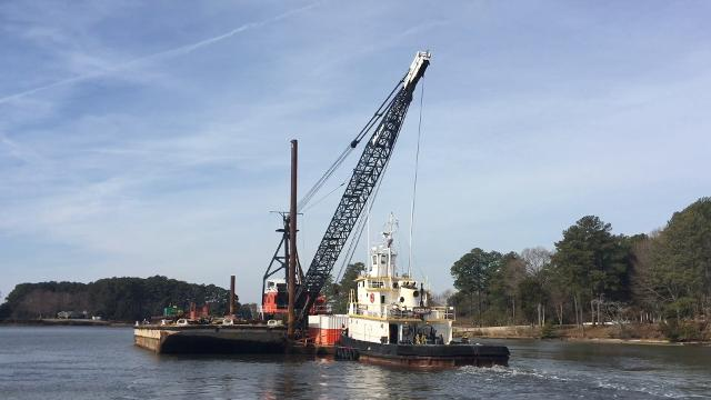 A tugboat moved a barge carrying a large crane out Onancock Creek on Friday, Feb. 8, 2018, after a bridge reconstruction project in Onancock, Virginia was completed ahead of schedule.
