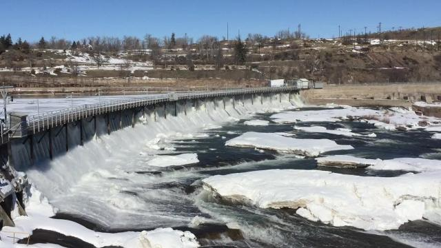 Water rushes through snow- and ice-covered dam on Missouri River