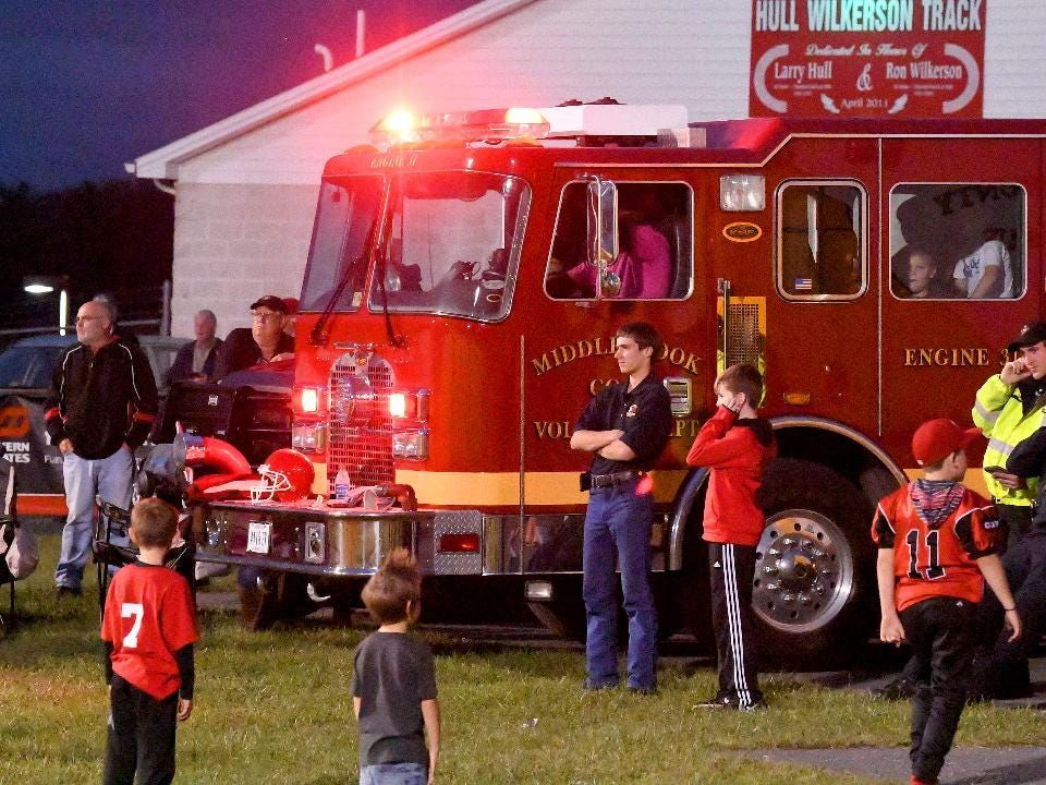 Volunteer firefighter Michael Gibson of the Middlebrook Volunteer Fire Department hits the lights and siren on the fire truck by the end zone each time Riverheads High School scores a touchdown.