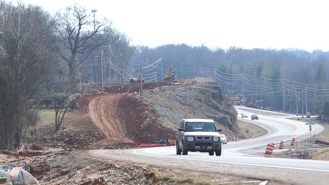 Cars drive down Warfield Blvd among road projects