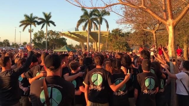 "As per tradition, the Marjory Stoneman Douglas marching band, the Eagle Regiment, performed ""Invincible,"" this time in honor of two bandmates killed in the school shooting on Feb. 14, 2018, Alex Schachter and Gina Montalto, during a candlelight vigil Feb. 15, 2018 at Pine Trails Park Amphitheater in Parkland."
