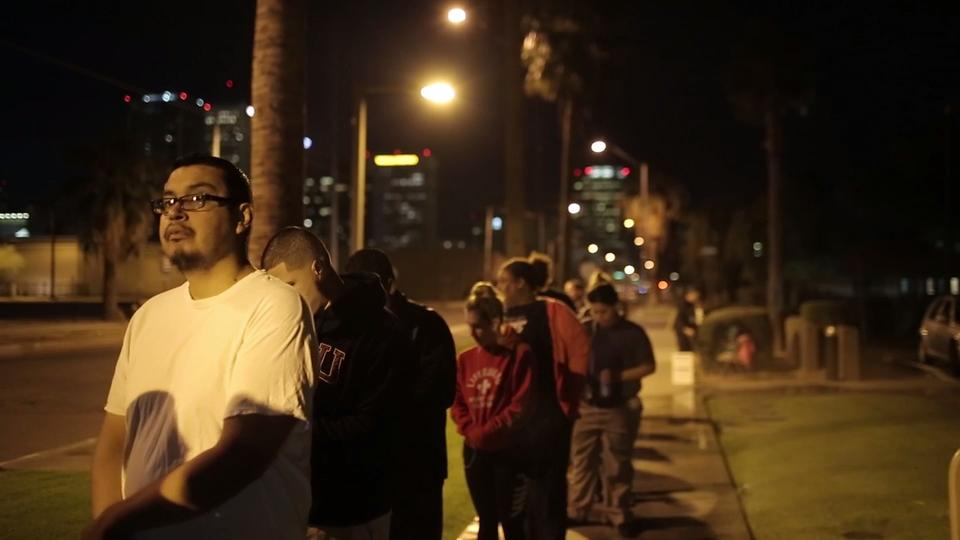 People stand in line to vote before the polls open in Phoenix