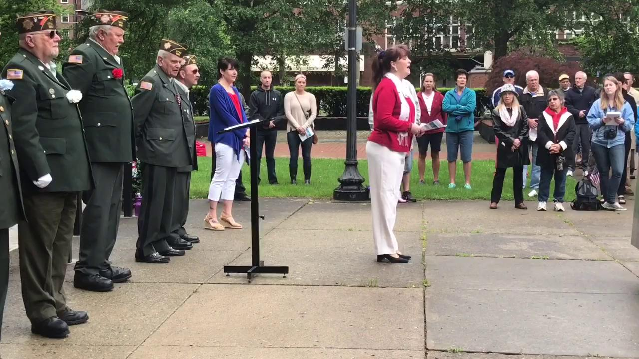 Lisa LaDieu of Ithaca leads the crowd gathered for the Memorial Day services in singing 'God Bless America' on Monday, May 29, at DeWitt Park in Ithaca.