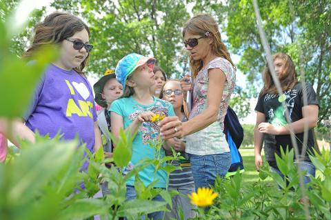 """Tracy Mc Dermott explains painting techniques to kids in the 8 to 12 year old range as part of a summer program """"Art In The Prairie"""" at the Gottfried Prairie and Arboretum on the UW-FDL campus. Wednesday, July 9, 2014."""