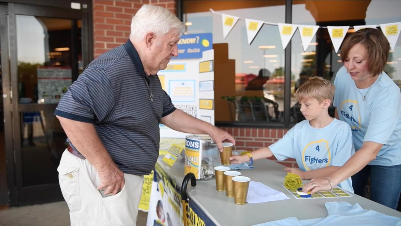 Four Simpsonville families are raising money to fund childhood cancer research by setting up a lemonade stand in front the Five Forks Bi-Lo.