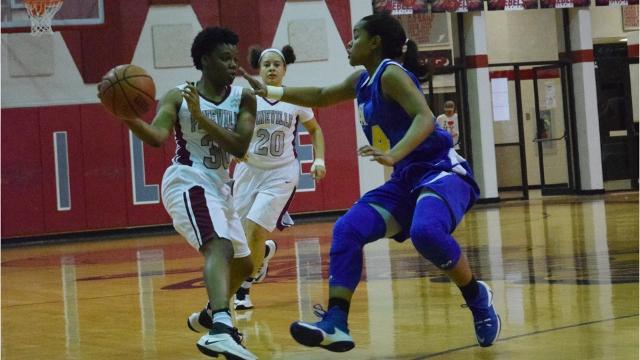 The Pineville High School girls' basketball team meets East Ascension on the court Monday.