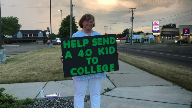 Mom puts herself on city street corner to raise money for daughter's college education.