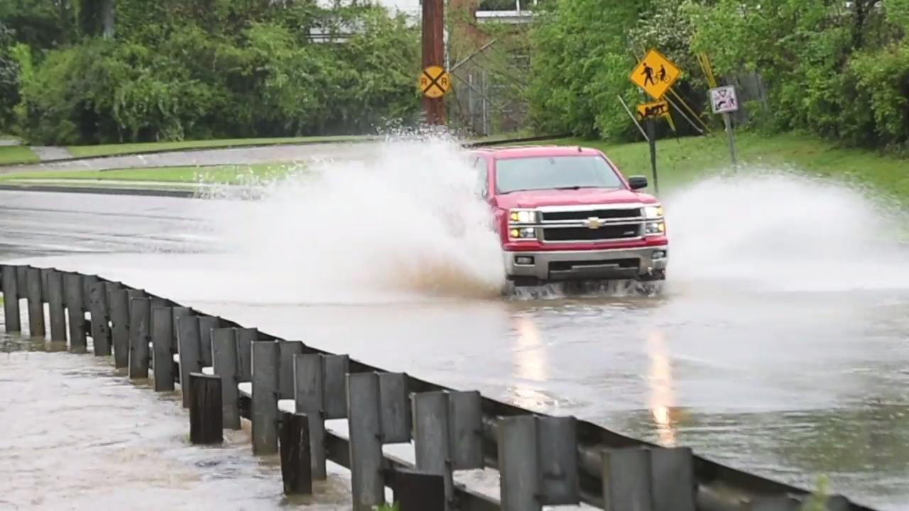 30 seconds of vehicles driving through a flooded section of road