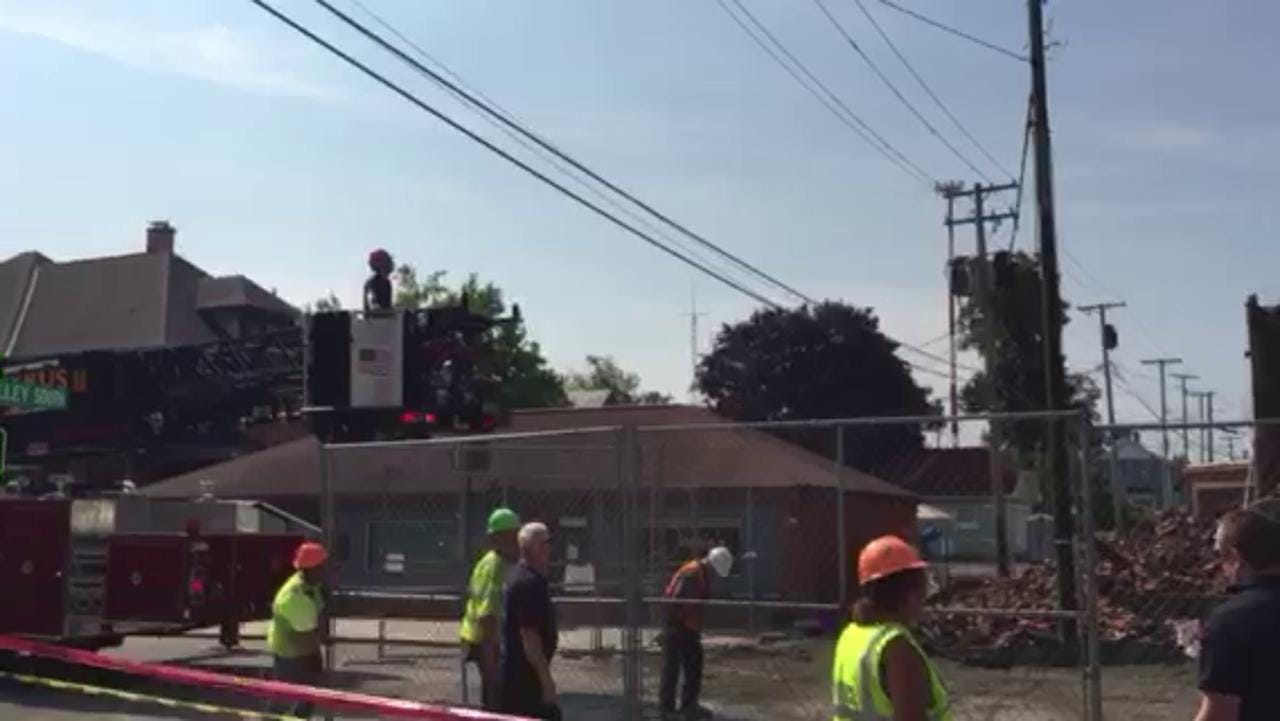 Demolition contractors and Bucyrus city firefighters prepare the site of the former Schine's Bucyrus Theater in downtown Bucyrus for further work on the building's steel beams Wednesday afternoon.