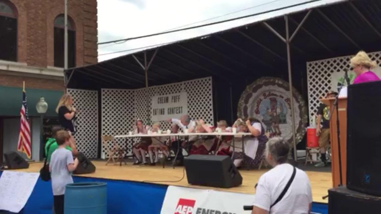 Bucyrus Mayor Jeff Reser, center, competes with Bratwurst Festival royalty in the cream puff-eating contest Friday, which he won.