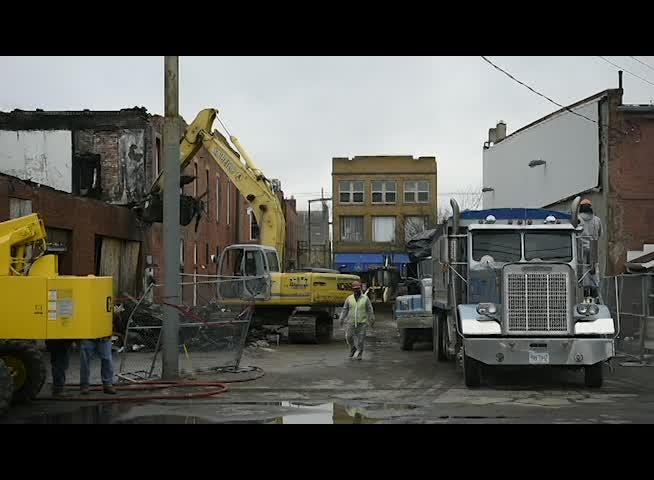 Demolition crews take down the burned out building at 146-148 Main St..