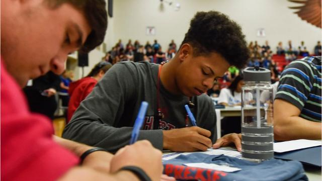 Marion Harding Seniors sign their commitment papers.
