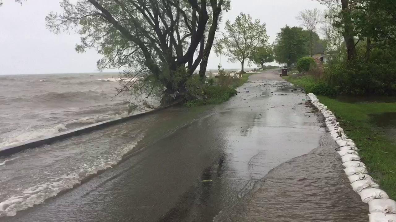 Lake Ontario waves roll over street in Parma