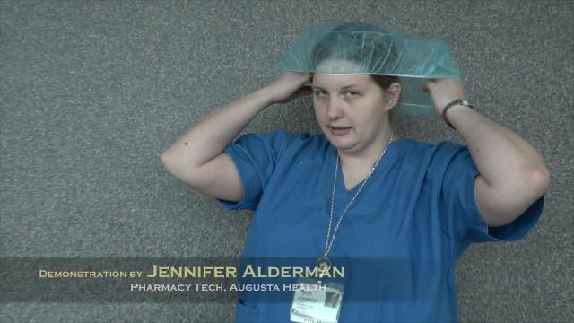 """Augusta Health's Jennifer Alderman demonstrates the """"garbing"""" process required before entering a pharmacy cleanroom, where sterile chemicals are mixed to create life-sustaining IV fluids."""