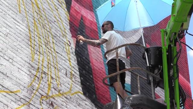 Eelco van den Berg, an artist from the Netherlands, is painting a mural on the side of a building on North Broadway in Yonkers.