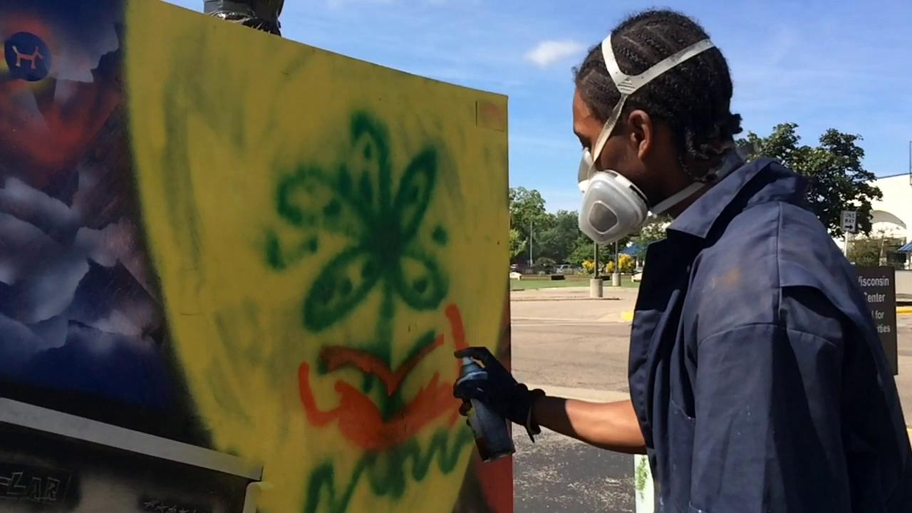 Stephon Freeman of Stevens Point encourages others to add to one of his pieces of art. The work is in the parking lot of the Central Wisconsin Cultural Center in Wisconsin Rapids. (Deb Cleworth/Aug. 5, 2015)